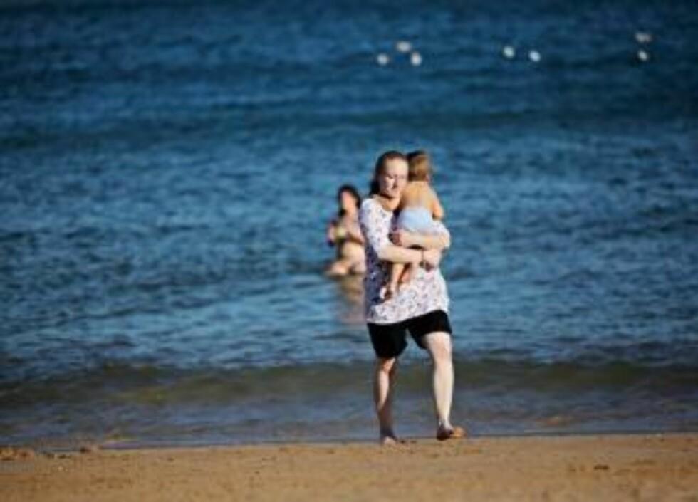 PÅ STRANDEN: Martin synes vannet er veldig kaldt. Her bærer mamma ham tilbake til den gode og varme sanden. FOTO: JON TERJE HELLGREN HANSEN