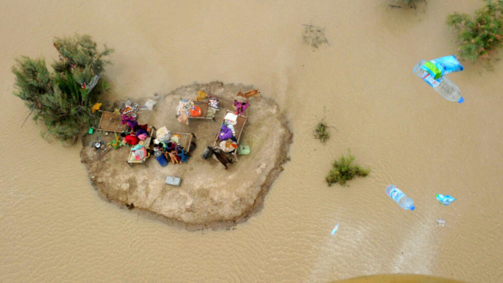<strong>FLOMKATASTROFE I PAKISTAN:</strong> Millioner av mennesker rammes av flommen i Pakistan. På bildet ser man barn og voksne som klamrer seg til en liten øy i flomvannet i den pakistanske byen Sukkur. Foto: AFP PHOTO/ASIF HASSAN
