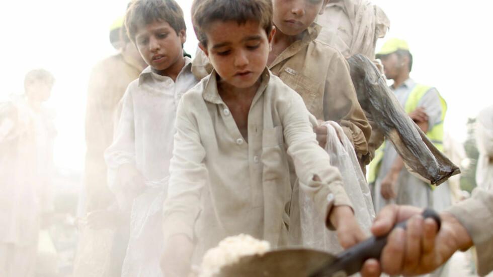 RAMMET AV FLOMMEN: Gutter venter på utdeling av mat nær Nowshera i den nordvestlige grenseprovinsen i Pakistan 23. august i år. Tre nye bøker gir et unikt innblikk i det folkerike landets altfor store utfordringer.   Foto: Reuters/Scanpix