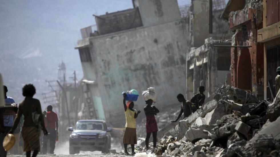 LETER ETTER MAT: Befolkningen i katastrofeområder springer ikke rundt i panikk, men gjør det som trengs. Katastrofeforskning viser at medmenneskeligheten er stor, folk setter ofte igang fellesmåltider, legger stridigheter til side, setter opp telt og hjelper dem som har det enda verre. Bildet er fra Port-au-Prince onsdag. Foto: AP/Ariana Cubillos