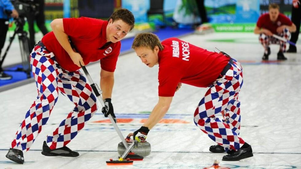 KOSTEKLOVNER: Torger Nergaard og Christoffer Svae (t.v.) koster en stein satt av Håvard Vad Petersson (i bakgrunnen) under kampen mot Canada. Foto: Tannen Maury, EPA/Scanpix