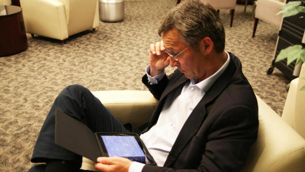KOMMER IKKE HJEM Her jobber Statsminister Jens Stoltenberg på det som må være hans nyinnkjøpte iPad mens han forgjeves venter på flyplassen utenfor New York. Nå har han tatt inn på hotell og må belage seg på å styre landet derfra. Foto: Statsministerens kontor.