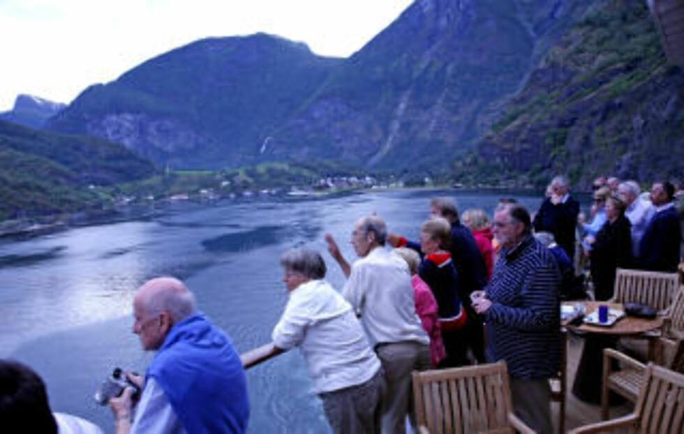 FJORDLAND: Entusiastiske passasjerer vinker seg ut fra Flåm.