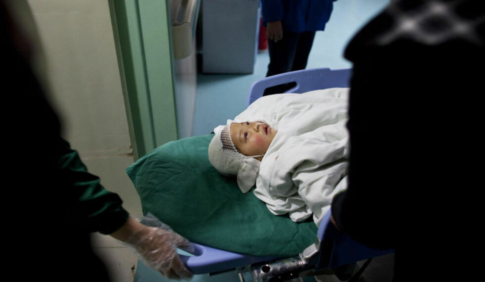 KNIVSTUKKET: Ei skadd jente fra barnehagen ankommer sykehuset i hjembyen Taixing. Foto: ALEXANDER F. YUAN/AP/SCANPIX