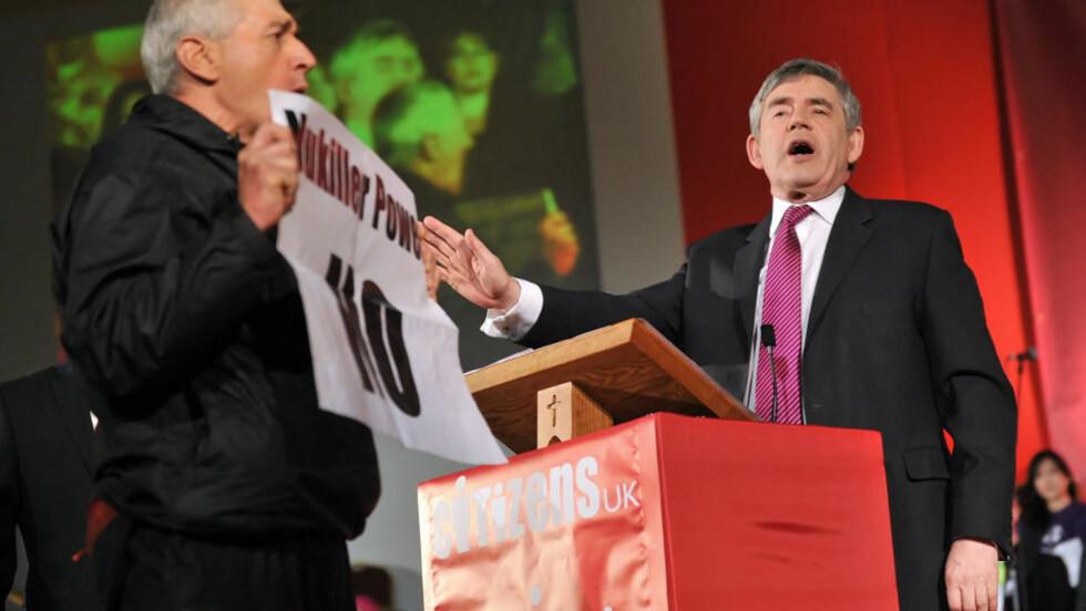 AVBRUTT: Den britiske statsministeren, Gordon Brown, forsøkte å fortsette sin tale da en demonstrant kom fram og opp på scenen under sin tale til medlemmer av forskjellige religiøse organisasjoner under dagens «Peoples' Assembly» organisert av grasrotorganisasjonen «Citizen UK». Foto: AFP PHOTO/Leon Neal/Scanpix