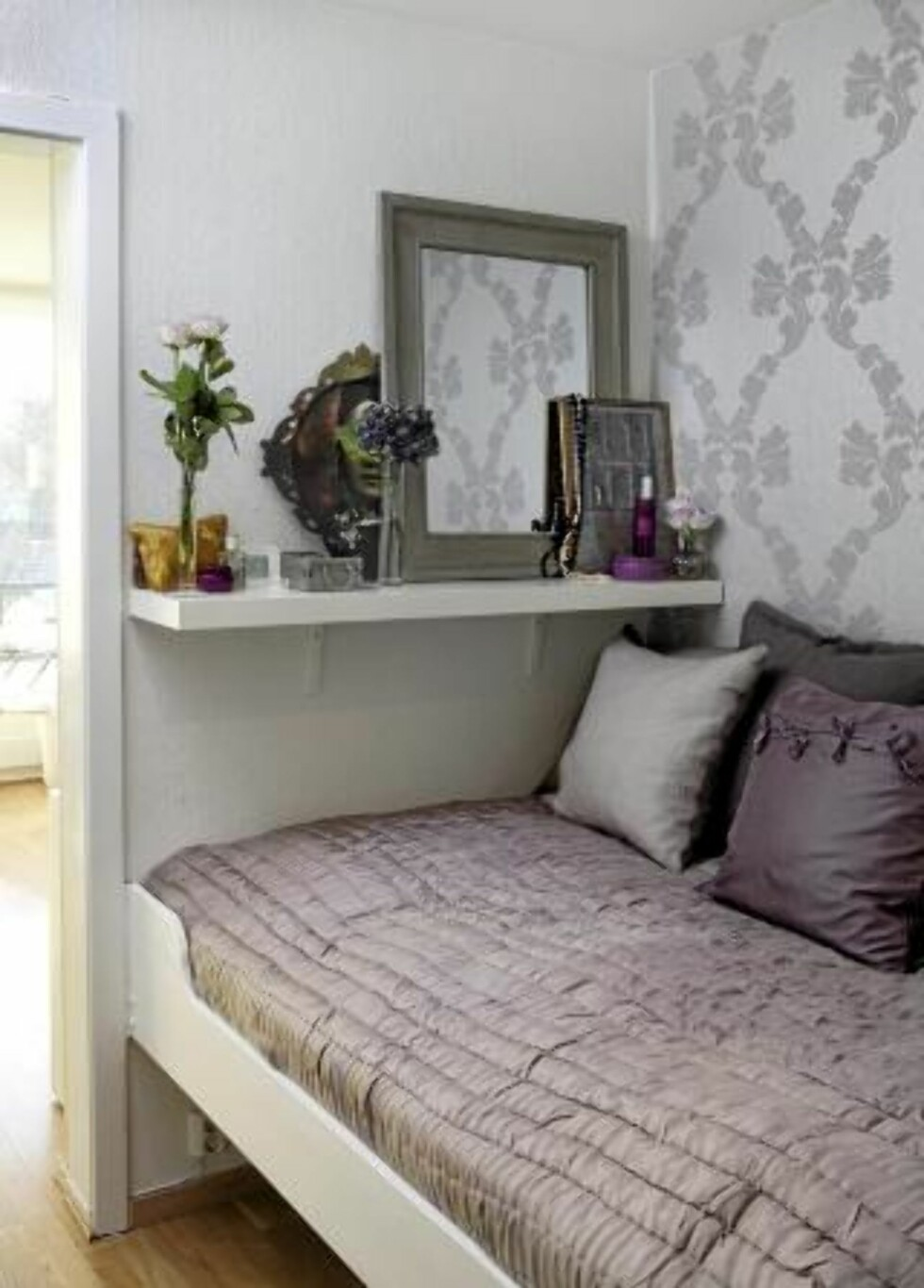 PLASSBYGD: En vegg i sovealkoven har fått et mønstret tapt Rococo Damask fra Cole & Son, som forhandles av John O. Borge. Sengen er plassbgd og har lagrinsmuligheter under. En enkel hylle over sengen erstatter nattbord.  FOTO: Yvonne Wilhelmsen