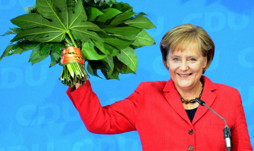 BLIR SITTENDE: Det skal mye til for at Angela Merkel ikke får en ny periode som forbundskansler i Tyskland - vel å merke for en ny sentrum-høyre-regjering i stedet for dagens storkoalisjon med Merkels kristendemokratiske CDU og sosialdemokratiske SPD. Her mottar den 55-årige valgvinneren partiets hyllest i Berlin i kveld. Foto: PEER GRIMM/EPA/SCANPIX