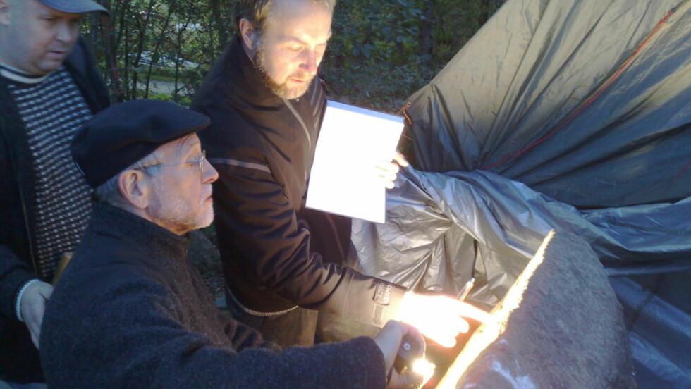 STUDERER STEINEN: Runologene James Knirk (til venstre) og Jonas Nordby studerer runesteinen. Bak står Frans-Arne Stylegar, fylkeskonservator i Vest-Agder fylkeskommune.  Foto: Erling Hægeland/dagbladet