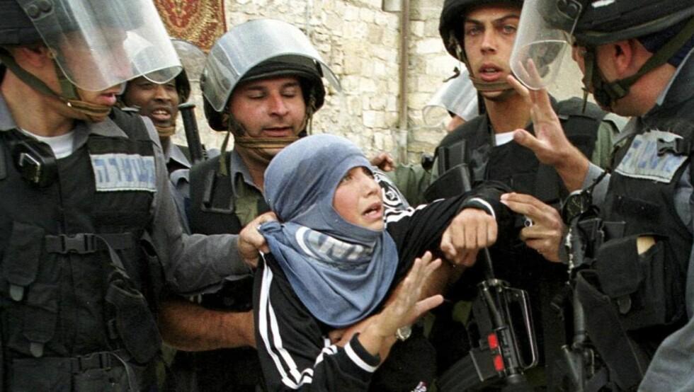FÅR KRITIKK: Her anholder israelske soldater en ung palestiner etter fredagsbønnen i gamlebyen i Jerusalem en oktoberdag i 2001. Nå får religionsfriheten i Israel skarp kritikk. Israel diskriminerer systematisk kristne og muslimer, kvinner og etniske minoriteter, slår amerikansk UD fast. Foto: REUTERS/Evelyn Hockstein/Scanpix