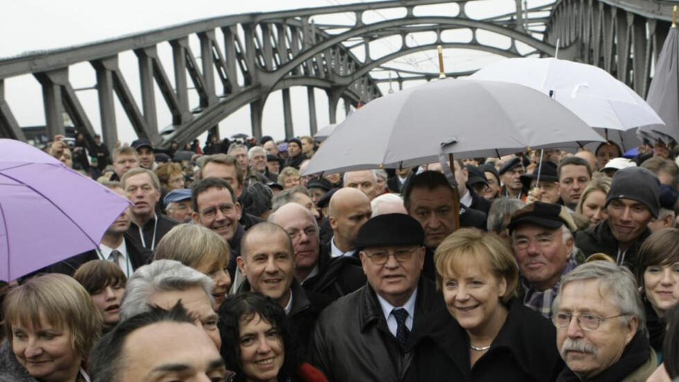 KRYSSET GRENSE: Tidligere i dag krysset Mikhail Gorbatsjov og Angela Merkel Bornholmer bro, som markerte grenseovergangen mellom øst og vest fram til 1989. Foto: AP Photo/Herbert Knosowski/SCANPIX