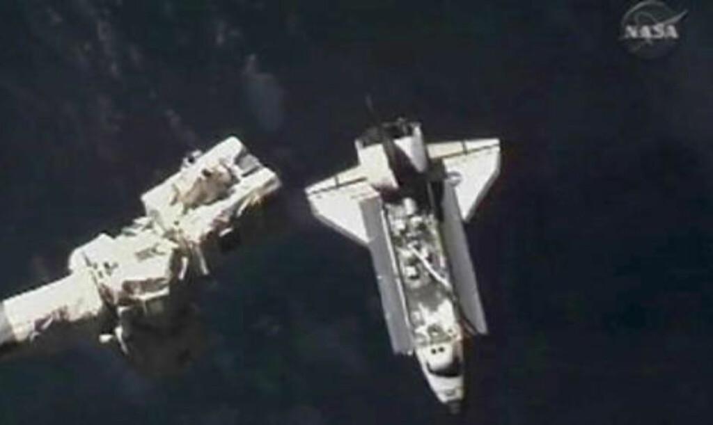 SAAAKTE: Atlantis nærmer seg ISS under den tidkrevende og ekstremt nøyaktige sammenkoblingsoperasjonen. Til venstre ser du ISS' robotarm. Foto: REUTERS/NASA TV/SCANPIX