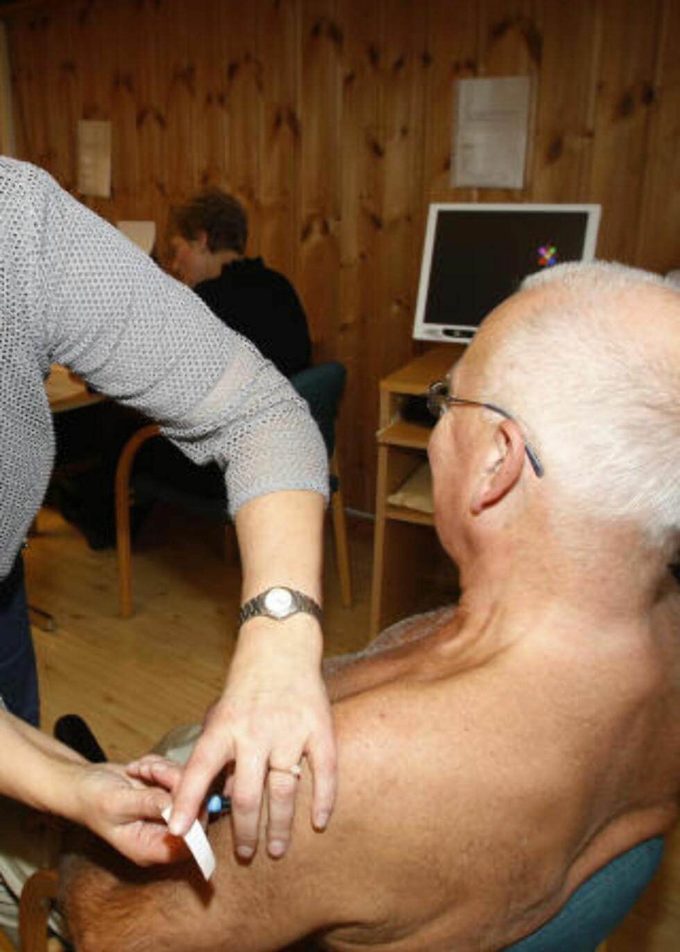 MENER VAKSINASJON ER FARLIG: Kveldens fakkeltog tror ikke helsemyndighetene spiller med åpne kort om vaksinen. Her får Steinar Bøye (75), en av flere hundre, influensavaksine på Stovner elderesenter onsdag. Foto: Morten Holm / SCANPIX .
