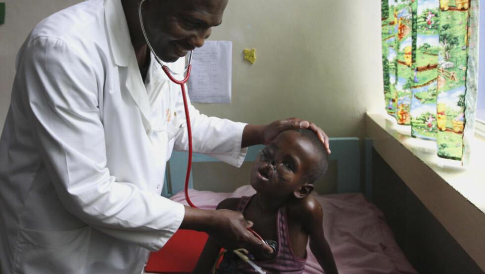 ANSIKTET AV EN USYNLIG KRIG: Ahmed Mohamed Mohamoud ble nok et uskyldig offer for krigshandlingene i Somalia. Her blir han undersøkt av doktor Igohwo Etuh ved et sykehus i Kijabe utenfor Nairobi i Kenya. Foto: AP Photo/Khalil Senosi/Scanpix