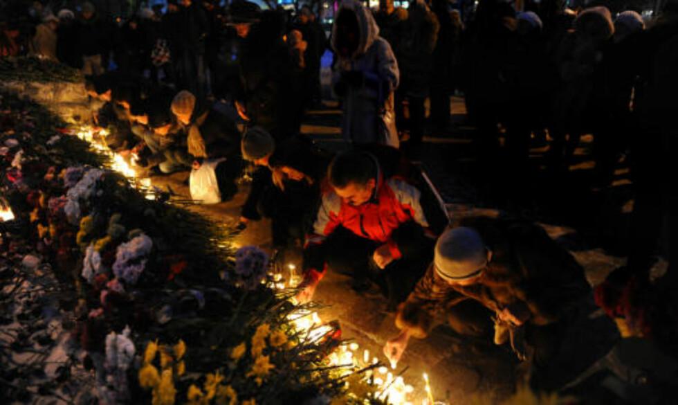 MINNES DE DØDE: Folk i byen Perm, 1150 kilometer øst for Moskva, la ned blomster og lys utenfor skandale-nattklubben. Foto: AFP PHOTO/DMITRY KOSTYUKOV/Scanpix