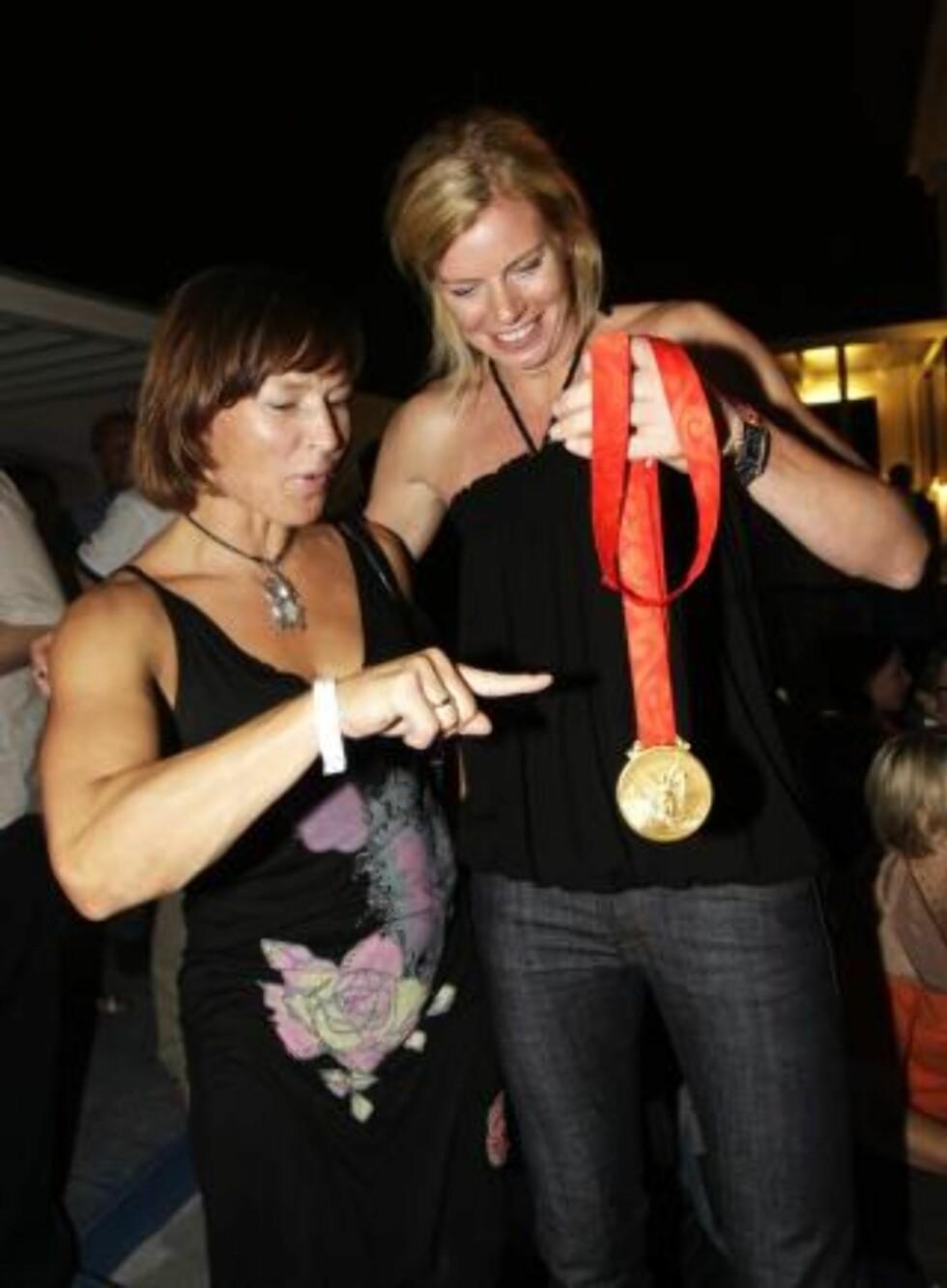 MANGLER OL-GULL: Tonje Larsen viser Susann Goksør Bjerkrheim gullmedaljen jentene vant i fjor. Susann har flest kamper, men Tonje har to gull eks-kapteinen ikke har - OL og EM. Foto: Erik Johansen/Scanpix