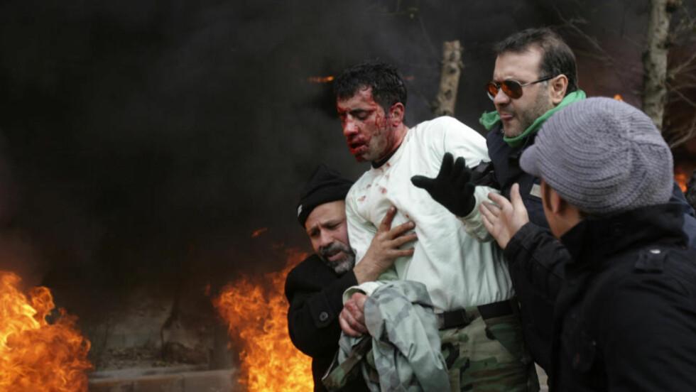 HARDE SAMMENSTØT: Demonstrasjonene mot regimet i Iran utviklet seg til blodige sammenstøt mellom demonstranter og sikkerhetsstyrker søndag. Her hjelpes en såret politimann vekk etter å blitt slått av demonstranter. Foto: REUTERS / SCANPIX