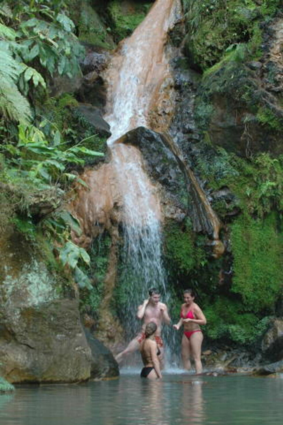 EVENTYR:  Kilden i Caldeira Velha kommer fra den gamle vulkanen Fogo. Denne trioen fra Storbritannia koste seg stort under det varme vannet. Navn: Kirsten Maisefield (22) i sort bikini, Rebecca O'Donald (24) i rød bikini og Brian Ellrich (24). Foto: Eivind Pedersen