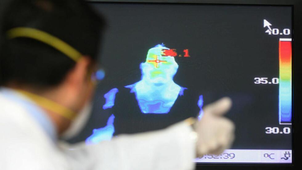 <strong>SPREDNINGSKONTROLL:</strong>: Flyplassansatte scanner etter syke med varmefølsomme kameraer, i et forsøk på å hindre spredning. Ingen tilfeller av H1N1-varianten som gir svineinfluensa er påvist i Norge. Foto:SCANPIX/AFP PHOTO/Carlos JASSO