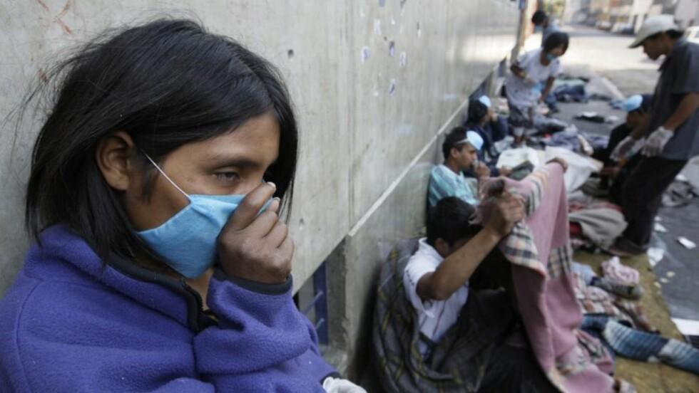 MEXICO CITY;  En hjemløs jente sniffer lim under en rutinesjekk for influensasymptomer i sentrum av Mexico City. Mexico har kommet over sykdommens toppunkt og er på vei tilbake, sier myndighetene. Foto: REUTERS/Daniel Aguilar