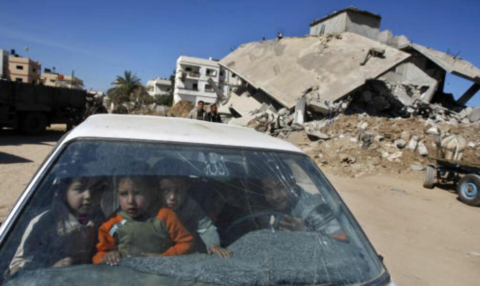 OMFATTENDE SKADE:  Den 22 dager lange krigen etterlot Gaza med betydelige merker. Her leker palestinske barn i en ødelagt bil foran et av husene som ble truffet av bomber. Foto: AFP PHOTO/MAHMUD HAMS