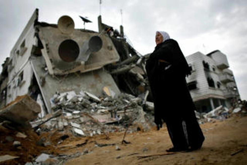 ØDELEGGELSER: En palestinsk kvinne går forbi ødelagte bygninger nord på Gazastripen, dagen etter at den 22 dager lange israelske offensiven var over. Foto: REUTERS/Jerry Lampen/SCANPIX