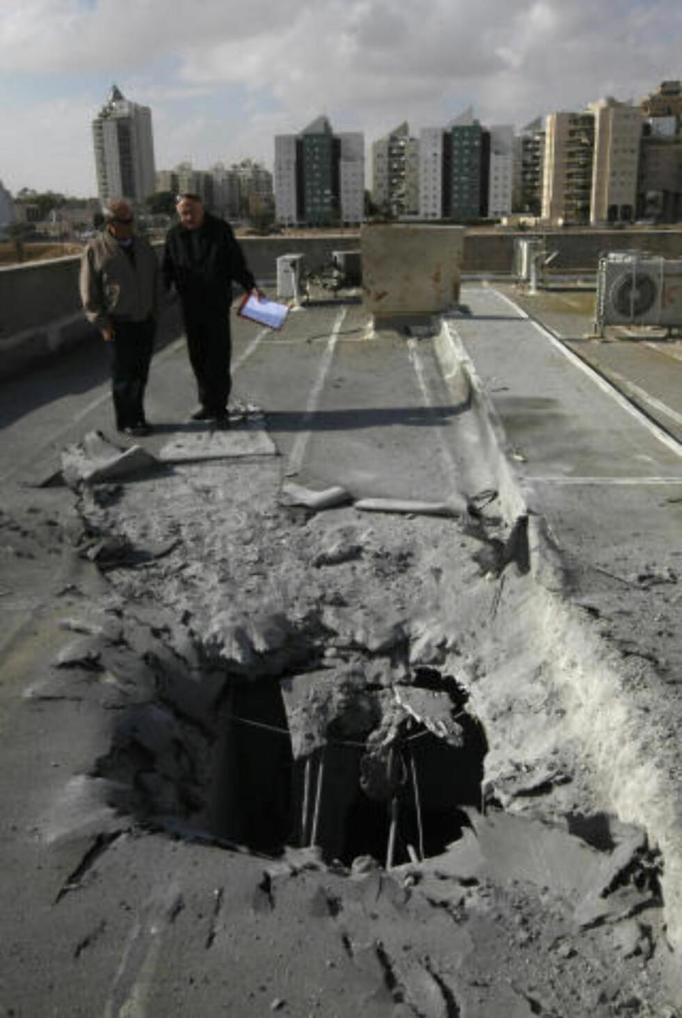 RAKETTANGREP: Israelere står ved stedet der et palestinsk rakettangrep har slått ned i byen Beersheva. De daglige rakettangrepene var en hovedårsakene til at den israelske offensiven ble innledet. Foto: AFP PHOTO/MENAHEM KAHANA/SCANPIX