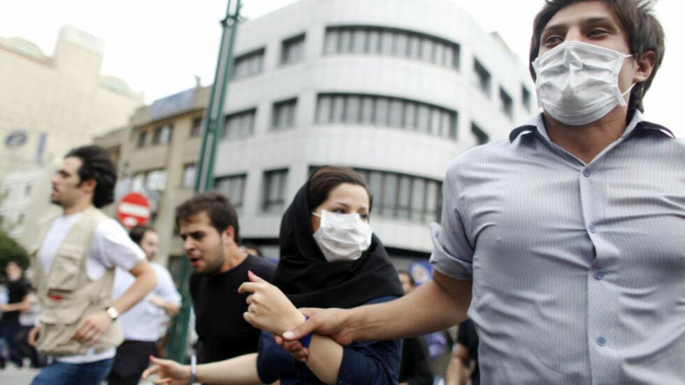 KNEBLET: Hundrevis av demonstranter ga uttrykk for hva de følte da de iført munnbind, gikk hånd i hånd gjennom Teherans gater i dag. Foto: REUTERS/Damir Sagolj/SCANPIX