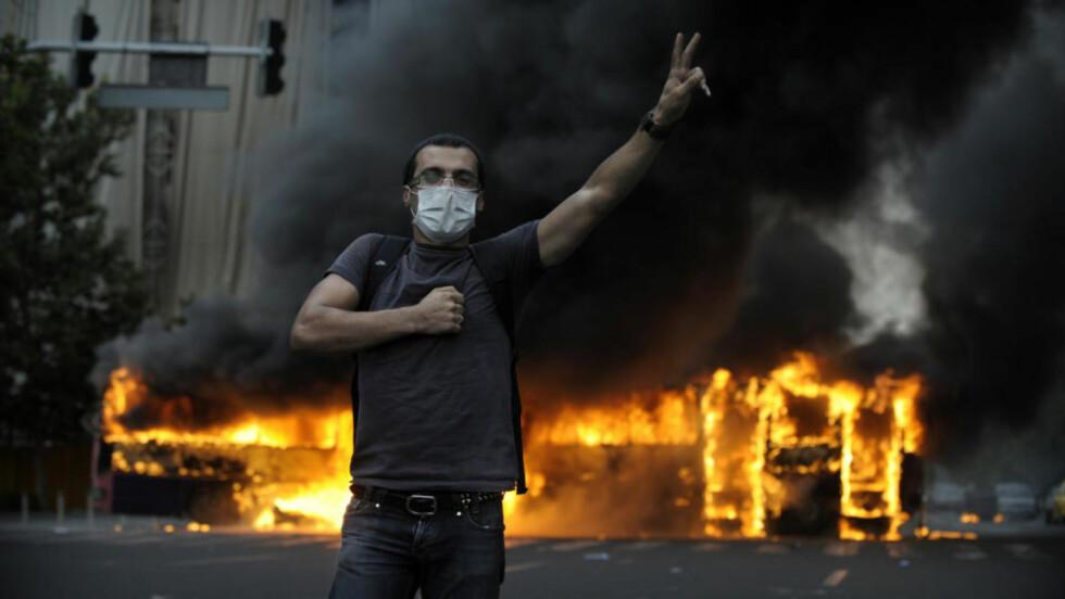 - NÅDD KOKEPUNKTET: En demonstrant står foran en brennende buss i Teherans gater. Iran opplever nå de største opptøyene siden den islamske revolusjonen i 1979, etter beskyldninger om at president Ahmadenijad kuppet valget. Foto: SCANPIX/AFP PHOTO/OLIVIER LABAN-MATTEI