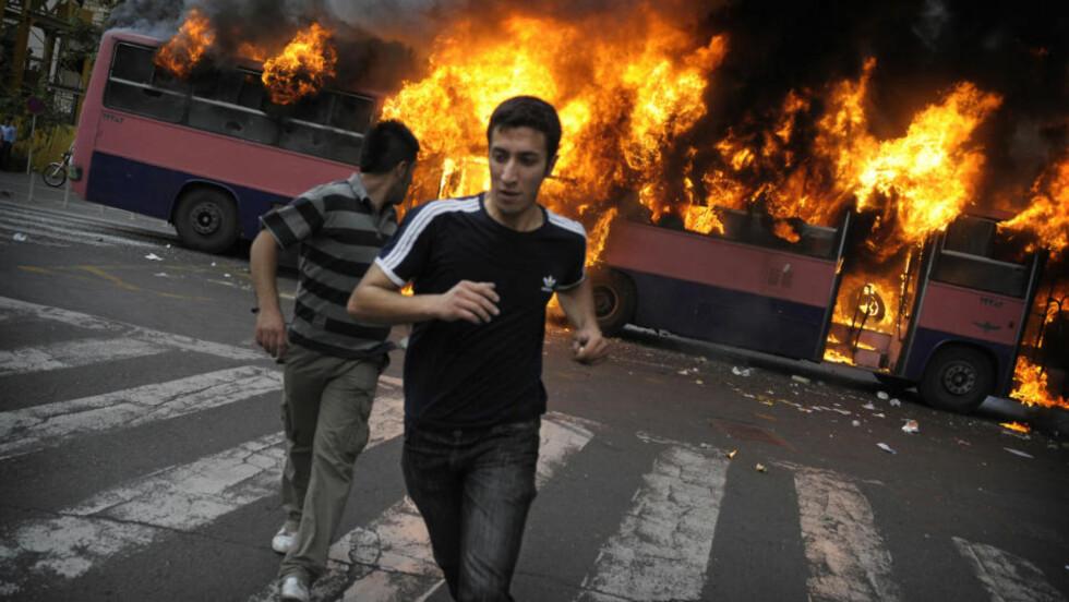 IRAN I FLAMMER: Tilhengere av presidentkandidat Mir Hossein Mousavi løper bort fra en buss som er satt fyr på i Teherans gater. Foto: AFP PHOTO/OLIVIER LABAN-MATTEI/SCANPIX