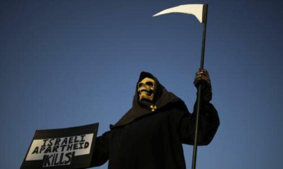 DEMONSTRANT  En amerikansk aktivist demonstrerer utenfor universitetet i Tel Aviv, der statsminister Benjamin Netanyahu i kveld kom med sitt betingede forslag om en palestinsk stat. Foto: AP/SCANPIX.