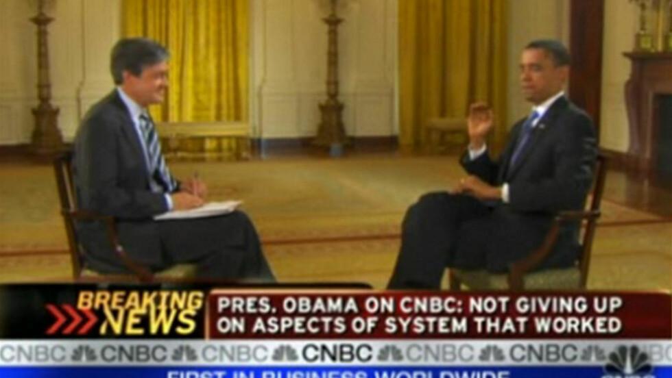 SMEKK! Bildet viser USAs president Barack Obama som er i ferd med å kverke en flue som svirrer foran ansiktet hans under et intervju. Til venstre sitter CNBCs korrespondent John Harwood, left. Foto: CBC/AP