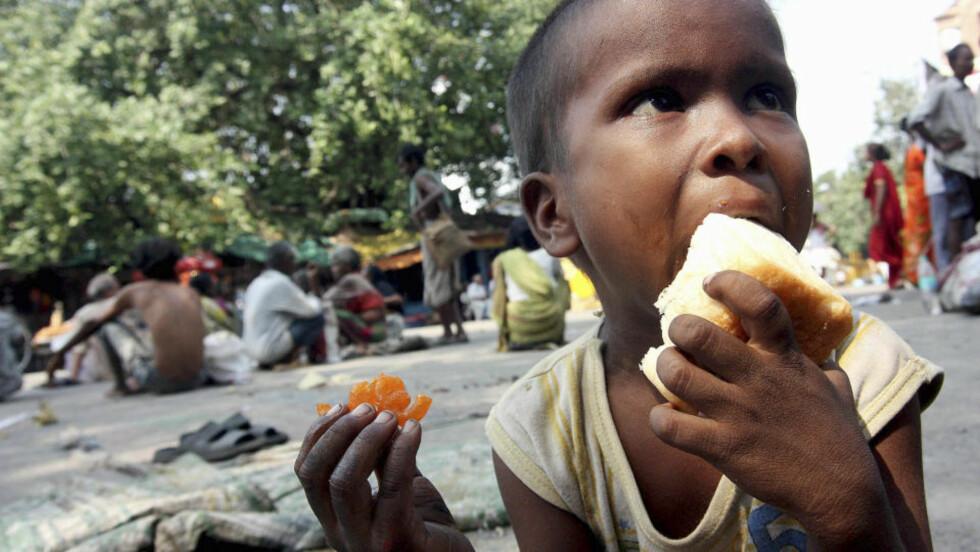 HAR FÅTT TAK I EN BRØDSKALK: Men denne lille, indiske gutten er en av mange i Asia som ikke har nok å spise. Asia, stillehavsområdet og Afrika sør for Sahara er hardest rammet av sultkrisen. Foto: AP Photo/Sucheta Das/Scanpix