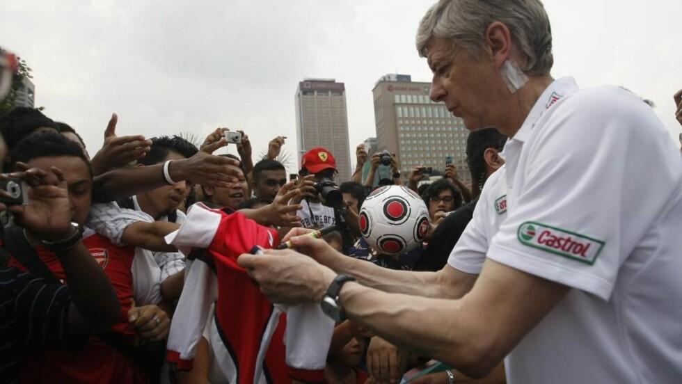 VIL KJØPE: Arsene Wenger jakter én spiller til, men ønsker ikke kvitte seg med noen spillere i sommer. Her skriver franskmannen autografer etter en treningsøkt med et malaysiske ungdomsfotballag. Foto: Syahrin Aziz / REUTERS.