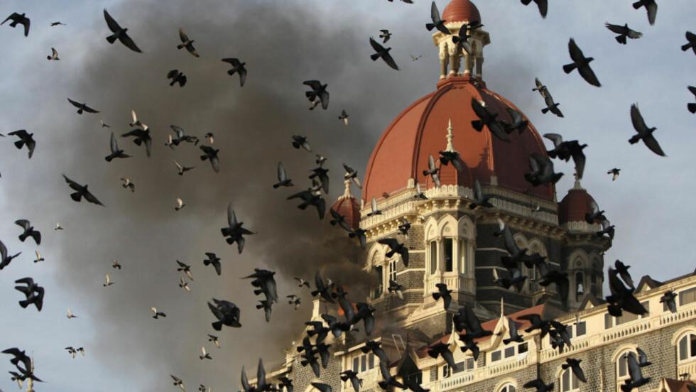 FLAMMER: Angrepet på Mumbai i november ifjor tok 166 liv. Her velter flammer ut av Taj Mahal-hotellet. India mistenker 22 pakistanske statsborgere for å stå bak angrepet. Foto: AFP PHOTO/Indranil MUKHERJEE/Scanpix