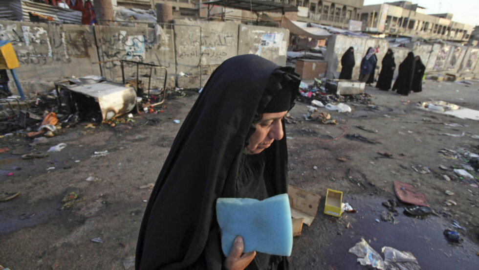 A woman is seen at the site of a bombing in the main Shiite district in Baghdad, Iraq, Thursday, June 25, 2009. A bomb ripped through a crowded market on Wednesday, less than a week before a deadline for U.S. combat troops to leave Iraq's urban areas. (AP Photo/Karim Kadim)