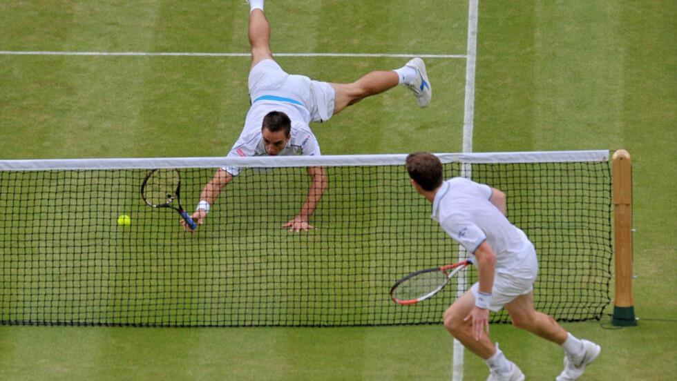 PÅ TRYNET: Serbiske Victor Troicki stuper forgjeves etter ballen i kampen mot Andy murray. Murray vant enkelt og er dermed klar for åttedelsfinalen på hjemmebane i Wimbledon. Foto: AFP