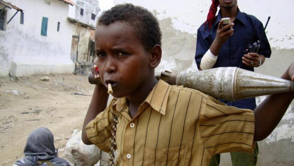 KRIG I GATENE: Et lite barn holder ammunisjon for krigere lojale til Hizbul Islamia. Bildet er tatt i Somalias hovedstad Mogadishu i dag. Foto: REUTERS/Omar Faruk/SCANPIX