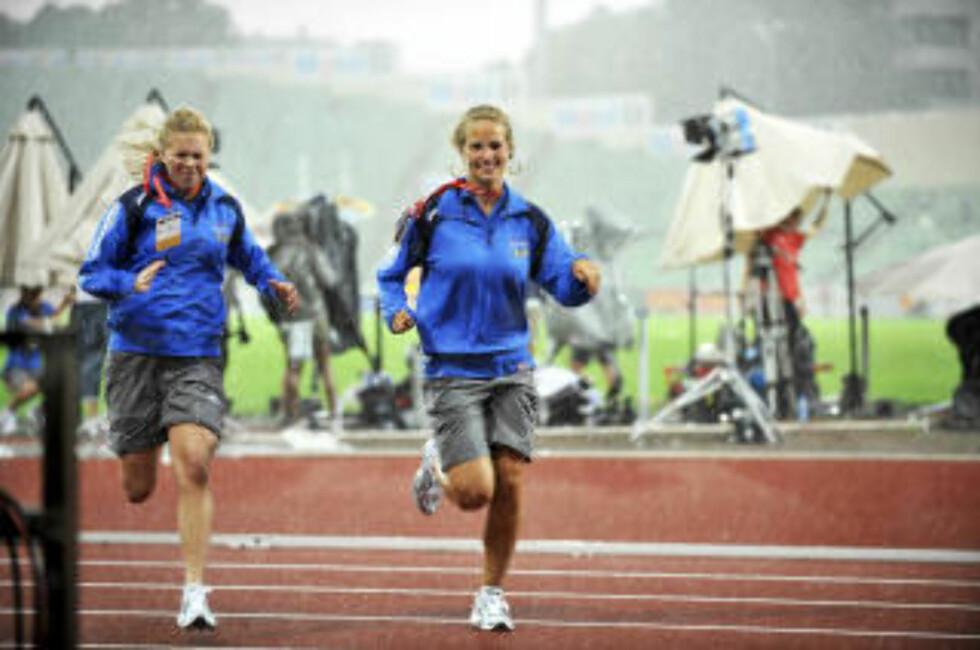MÅTTE RØMME UNNA: Disse jentene måtet søke ly da regn og torden braket løs over Bislett stadion. Foto: ERIK BERGLUND
