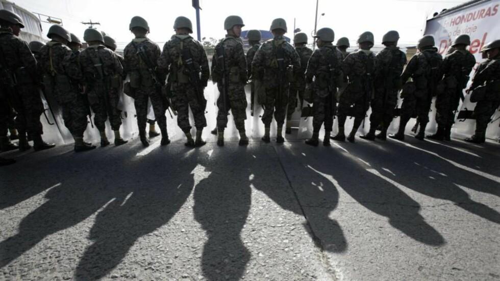 FRYKTER BLODBAD: Politi og soldater holder øye med demonstranter som protesterer mot militærkuppet i Honduras. Det er frykt for at det kan komme til sammenstøt mellom motstandere og tilhengere av kuppet når president Manuel Zelaya etter planen vender hjem søndag. Foto: REUTERS / Oswaldo Rivas / SCANPIX