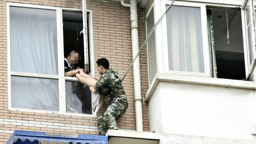 REDDET JENTA: Den 22 år gamle brannmannen, kledd i militæruniform, klarte å redde jenta ut av farens grep. Foto: REUTERS/China Daily/Scanpix