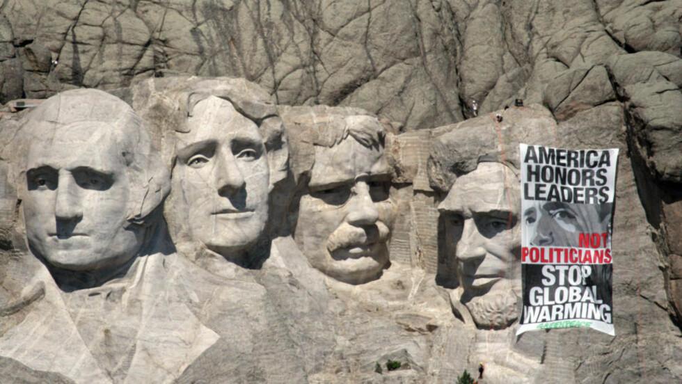 FEM PRESIDENTER: Fem kjente hoder prydet Mount Rushmore i går onsdag. De permanente ansiktene til George Washington, Thomas Jefferson, Theodore Roosevelt og Abraham Lincoln fikk besøk av Barack Obama, takket være Greenpeace. Foto: AFP PHOTO