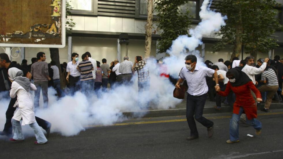 TÅREGASS: Det er dramatisk i gatene i Teheran. Dette bildet er tatt 9. juli, men politiet bruker også i dag tåregass og batonger mot demonstrantene. Foto: AP Photo/Scanpix