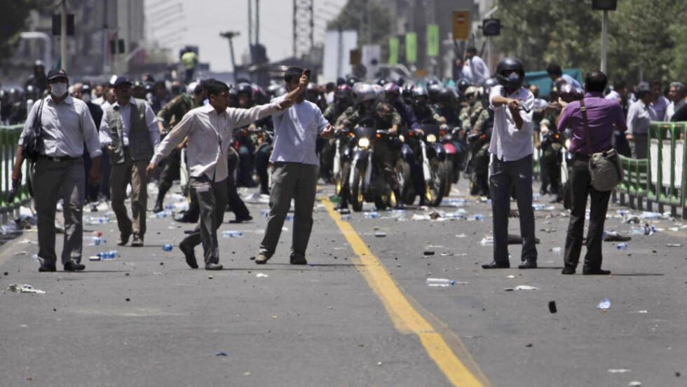 TÅREGASS: Dette bildet viser et militsmedlem som retter et tåregassvåpen mot en av demonstrantene utenfor universitetet i Teheran fredag. På grunn av at mediene ikke har tilgang til Iran, sender nyhetsbyråene nå ut en del bilder som er tatt av ulike personer i Iran, og det er derfor ikke bekreftet av dem at bildet er tatt i dag. Foto:  AP/SCANPIX