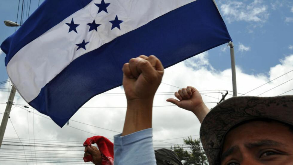 DEMONSTRERER: Zelaya-tilhengere protesterer mot kuppregimet i Honduras i Tegucigalpa lørdag. Zelaya har lenge blitt nektet å komme inn i sitt eget land. Nå ønsker han samlingsregjering. Foto: AFP PHOTO/ Yuri CORTEZ/Scanpix