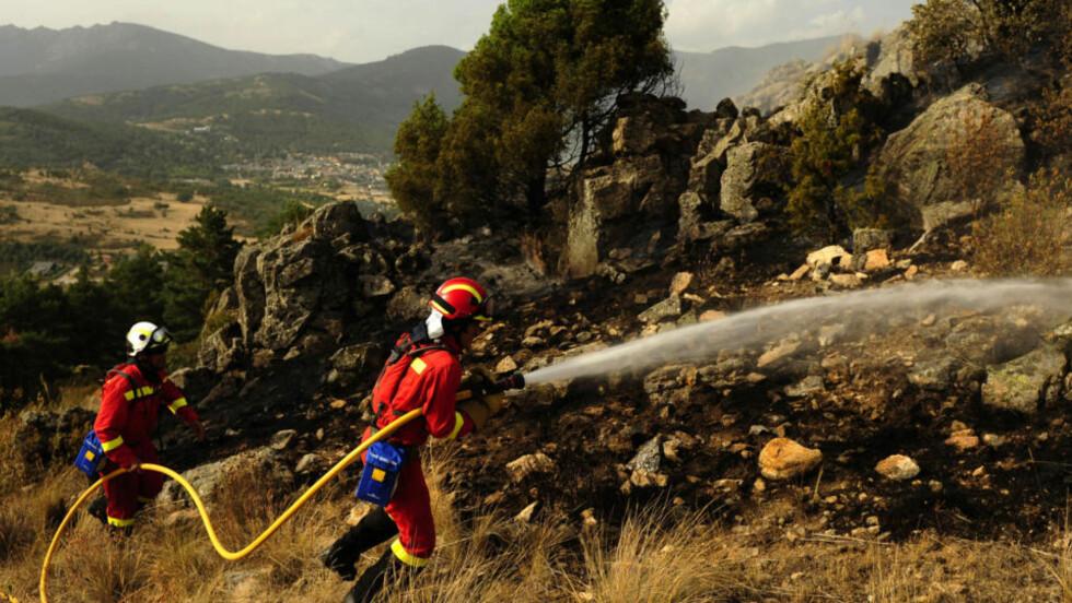 TIL KRIG MOT FLAMMENE: Den spanske militære beredskapstroppen UME prøver å slokke skogbrannen i Cerro del Castillo nær byen Collado Mediado, nordvest for Madrid. Rundt 2000 mennesker har måttet avekuere byen. Fire brannmenn har blitt drept, mens to har blitt alvorlig skadet i kampene. Foto: AFP PHOTO / PEDRO ARMESTRE / Scanpix