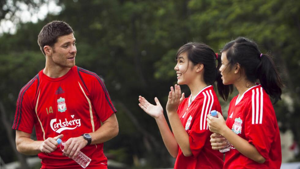- BØR BLI: Rafa Benitez' ber Xabi Alonso (venstre) lytte til fansen som ønsker at spanjolen skal bli værende på Merseyside. Her er Alonso i samtale med to Singaporske supportere.  Foto: AP Photo/John Heng/Scanpix