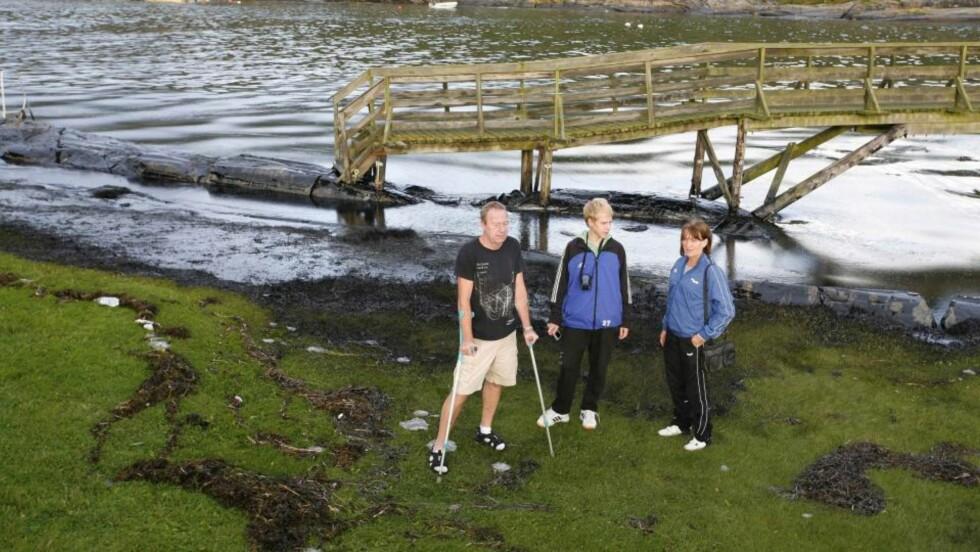 ØDELEGGELSER: Jørn Nilsen (t.v.), Aud Eklund og Joachim Andersen kan konstatere at badestranda deres er ødelagt av olje. Foto: Per Flåthe
