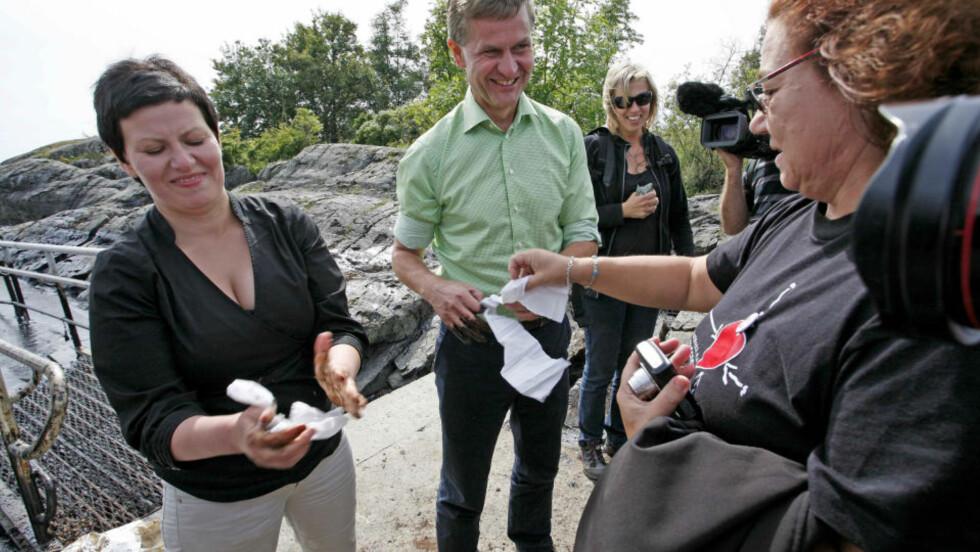 FYSJ, DA: Ministrene forsøker å tørke vekk oljesøl fra hendene. De to lover å rydde opp, men nekter å la oljesølet påvirke oljeletingsspørsmålet i Nord-Norge. Foto: Per Flåthe