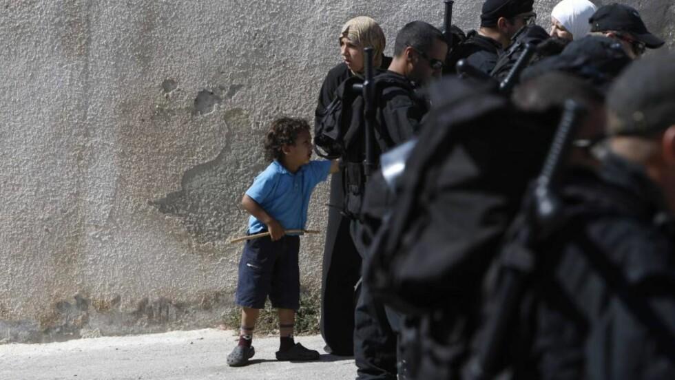 KASTET UT AV HUSET FAMILIEN EIDE I 50 ÅR: Maysoon al-Rawi står sammen med sin fire år gamle sønn Adam bak de israelske soldatene som søndag kastet dem ut av huset deres i Øst-Jerusalem. Norge reagerer på utkastelsen av to palestinske storfamilier. Foto: REUTERS / Ronen Zvulun / SCANPIX