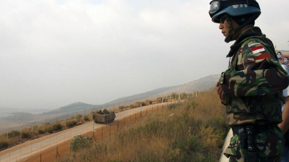 NY KONFLIKT KAN BLUSSE OPP: En indonesisk FN-soldat ser ned på et israelsk militærkjøretøy ved grensen til Libanon. Israel advarer mot at en ny konflikt med Hizbollah kan blusse opp når som helst. Foto: REUTERS / Ali Hashisho / SCANPIX